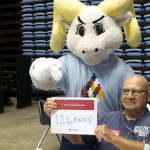 Ramses points to a sign held by a donor reading 126 pints!