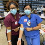 Two health care works show their bandaged arms after giving blood